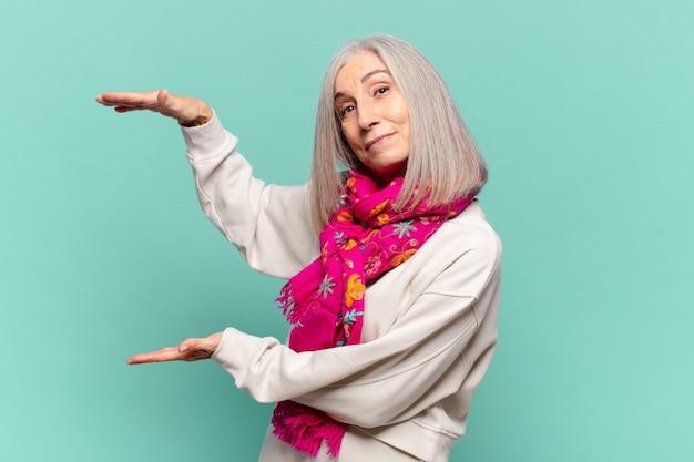 Donna di mezza età che tiene un oggetto con entrambe le mani sullo spazio della copia laterale, mostra, offre o pubblicizza un oggetto