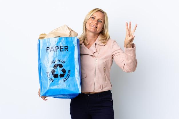 Donna di mezza età che tiene un sacchetto di riciclaggio pieno di carta da riciclare isolato su bianco felice e contando tre con le dita