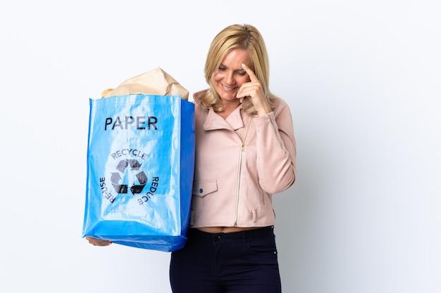 Donna di mezza età che tiene un sacchetto di riciclaggio pieno di carta da riciclare isolata sulla risata bianca
