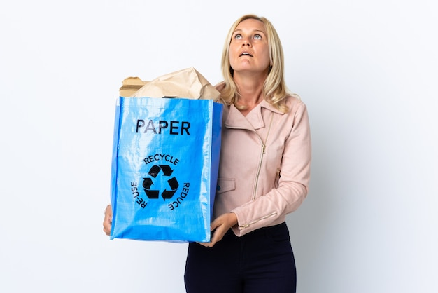 Donna di mezza età che tiene un sacchetto di riciclaggio pieno di carta da riciclare isolato su bianco che osserva in su e con espressione sorpresa