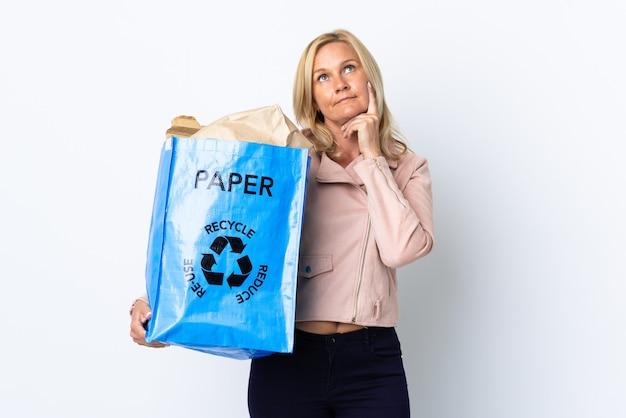 Donna di mezza età che tiene un sacchetto di riciclaggio pieno di carta da riciclare isolato su bianco pensando un'idea mentre osservava