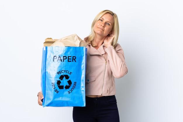 Donna di mezza età che tiene un sacchetto di riciclaggio pieno di carta da riciclare isolato sulla parete bianca che ha dubbi