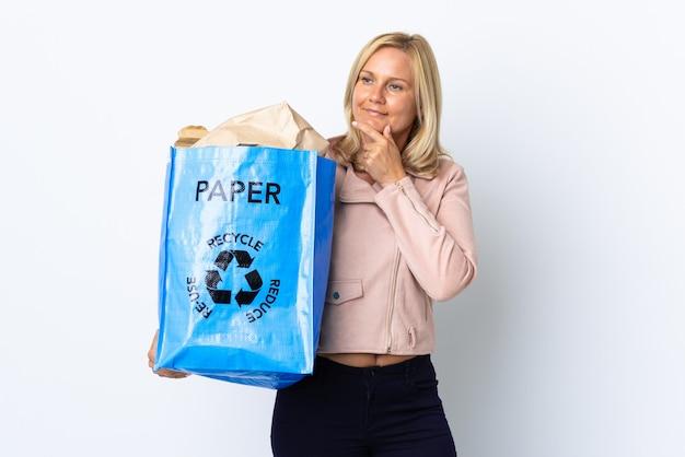 Donna di mezza età che tiene un sacchetto di riciclaggio pieno di carta da riciclare isolato sul muro bianco che guarda al lato e sorridente