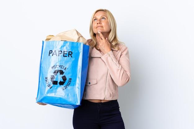 Donna di mezza età che tiene un sacchetto di riciclaggio pieno di carta da riciclare isolato sulla parete bianca che osserva in su mentre sorride