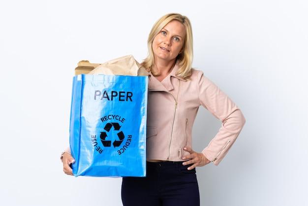 Donna di mezza età che tiene un sacchetto di riciclaggio pieno di carta da riciclare isolato sul muro bianco in posa con le braccia all'anca e sorridente