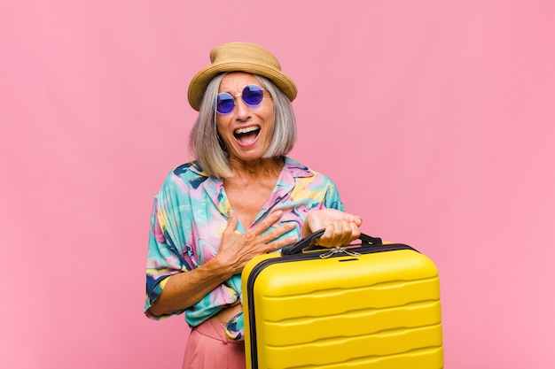Donna di mezza età che ride ad alta voce a uno scherzo esilarante, si sente felice e allegra, si diverte