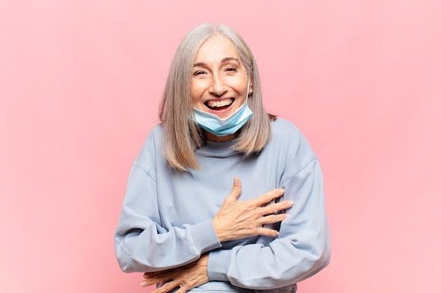 Donna di mezza età che ride ad alta voce a uno scherzo esilarante sentendosi felice e allegra divertendosi