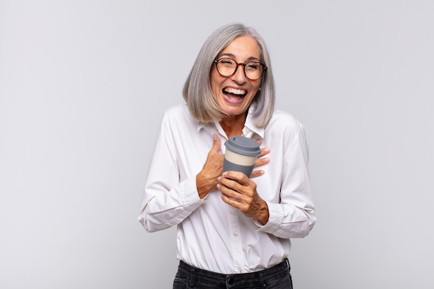 Donna di mezza età che ride ad alta voce a uno scherzo esilarante