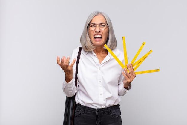 Donna di mezza età che sembra urlando arrabbiata, irritata e frustrata