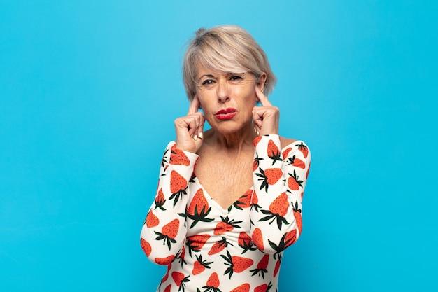 Donna di mezza età che sembra arrabbiata, stressata e infastidita, coprendo entrambe le orecchie con un rumore assordante, suono o musica ad alto volume