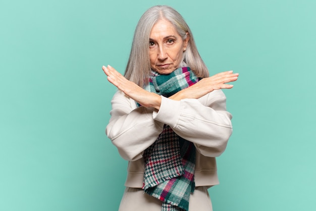 Donna di mezza età che sembra infastidita e stanca del tuo atteggiamento, dicendo basta! mani incrociate davanti, dicendoti di fermarti