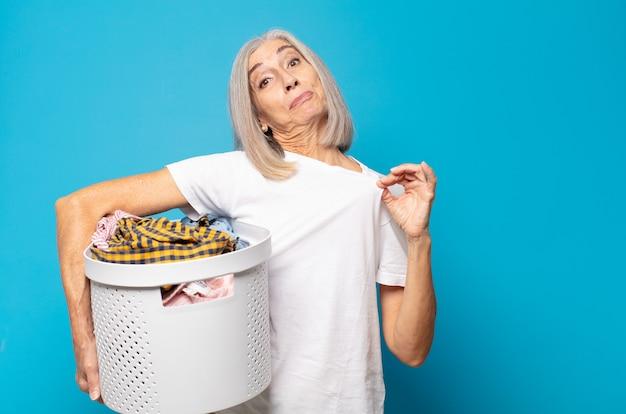 Donna di mezza età che sembra arrogante, di successo, positiva e orgogliosa, indicando se stessa