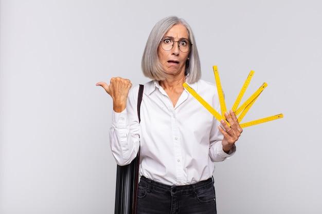 Donna di mezza età che guarda sbalordita incredula, indicando un oggetto sul lato e dicendo wow, incredibile. concetto di architetto