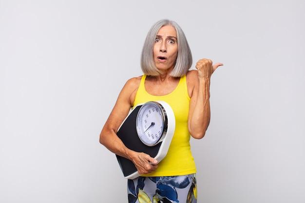 Donna di mezza età che guarda sbalordita incredula, indicando un oggetto sul lato e dicendo wow, incredibile. concetto di fitness