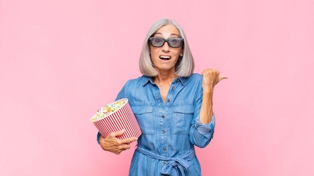 Donna di mezza età che guarda stupita incredula, indicando un oggetto sul lato e dicendo wow, incredibile concetto di film