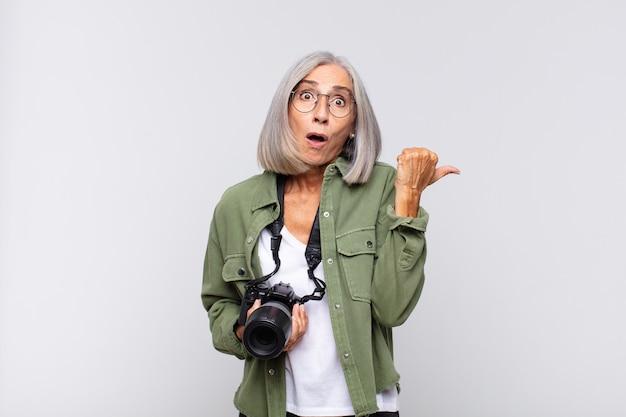 Donna di mezza età che guarda sbalordita incredula, indicando un oggetto sul lato e dicendo wow, incredibile. concetto di fotografo