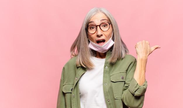 Donna di mezza età che guarda sbalordita incredula, indicando un oggetto sul lato e dicendo wow, incredibile
