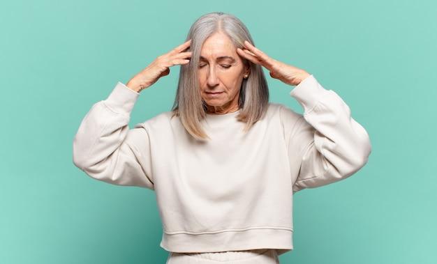 Donna di mezza età dall'aspetto concentrato, riflessivo e ispirato, che fa brainstorming e immagina con le mani sulla fronte