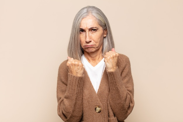 Donna di mezza età che sembra sicura, arrabbiata, forte e aggressiva, con i pugni pronti a combattere in posizione di boxe