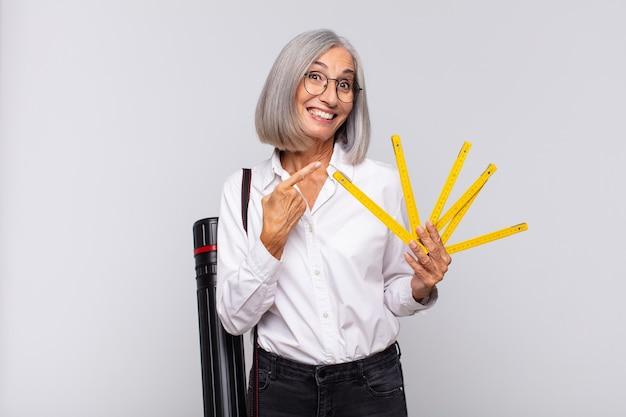 Donna di mezza età che sembra eccitata e sorpresa che punta di lato e verso l'alto per copiare lo spazio