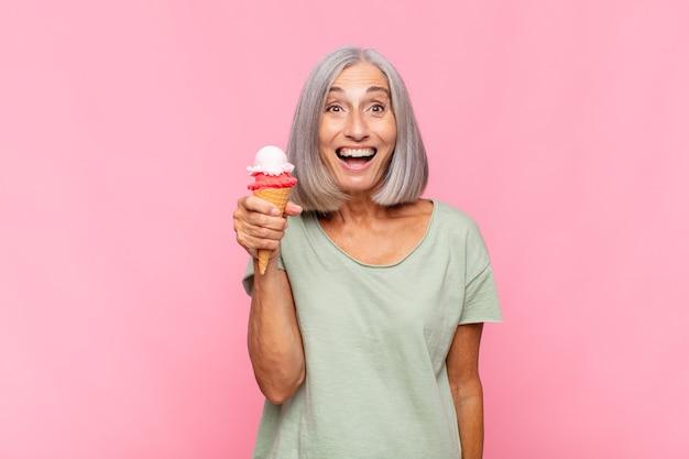 Donna di mezza età che sembra felice e piacevolmente sorpresa, eccitata da un'espressione affascinata e scioccata mentre mangia un gelato
