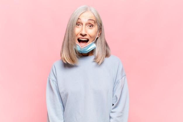 Donna di mezza età che sembra felice e piacevolmente sorpresa, eccitata da un'espressione affascinata e scioccata
