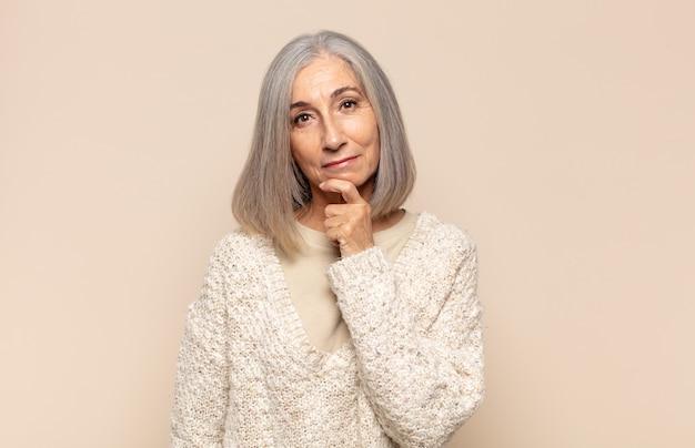 Donna di mezza età che sembra felice e sorridente con la mano sul mento, chiedendosi o facendo una domanda, confrontando le opzioni