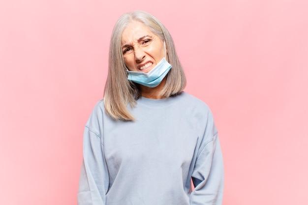 Donna di mezza età che guarda il labbro mordace perplesso e confuso con un gesto nervoso che non conosce la risposta al problema
