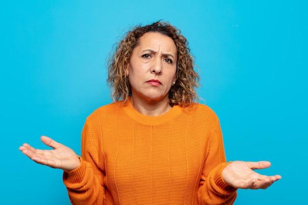 Donna di mezza età che sembra perplessa, confusa e stressata, chiedendosi tra diverse opzioni, sentendosi incerta
