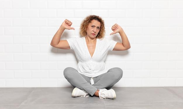 Donna di mezza età che sembra triste, delusa o arrabbiata, che mostra i pollici verso il basso in disaccordo, sentendosi frustrata