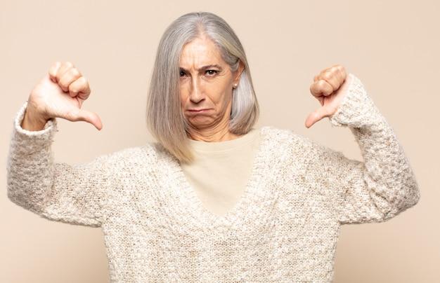 Donna di mezza età che sembra triste, delusa o arrabbiata, che mostra i pollici in disaccordo, sentendosi frustrata