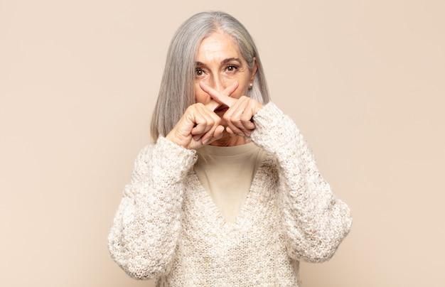 Donna di mezza età dall'aria seria e scontenta con entrambe le dita incrociate davanti in segno di rifiuto, chiedendo silenzio
