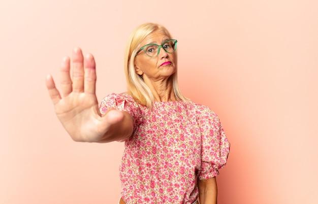 Donna di mezza età che sembra seria, severa, dispiaciuta e arrabbiata che mostra il palmo aperto che fa gesto di arresto