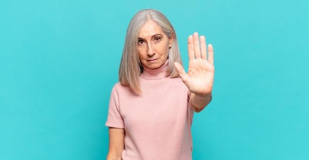 Donna di mezza età che sembra seria, severa, dispiaciuta e arrabbiata che mostra il palmo aperto che fa il gesto di arresto