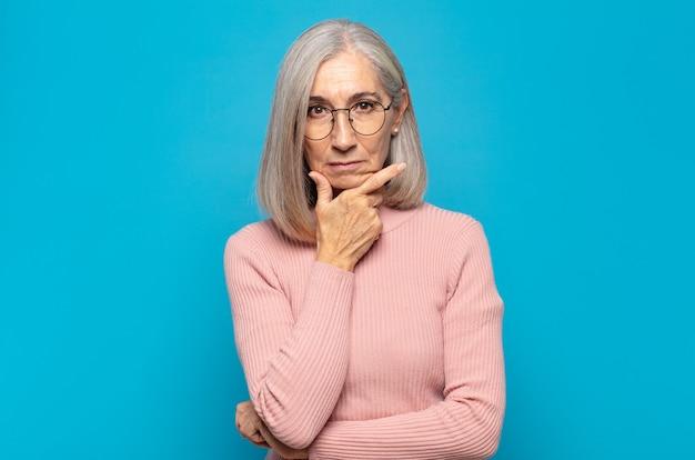 Donna di mezza età dall'aspetto serio, premuroso e diffidente, con un braccio incrociato e una mano sul mento, opzioni di ponderazione