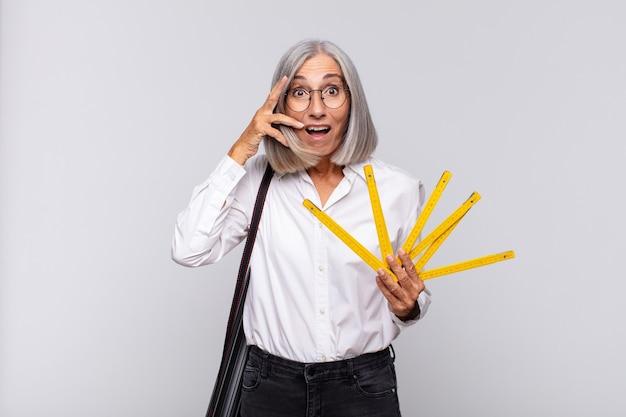 Donna di mezza età che sembra scioccata, spaventata o terrorizzata, coprendosi il viso con la mano e sbirciando tra le dita. concetto di architetto