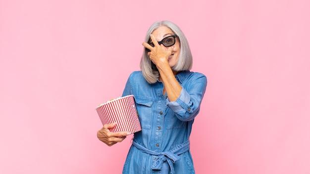 Donna di mezza età che sembra scioccata, spaventata o terrorizzata, coprendo il viso con la mano