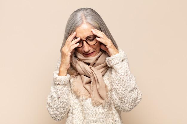 Donna di mezza età che sembra stressata e frustrata, lavora sotto pressione con un mal di testa e tormentata dai problemi