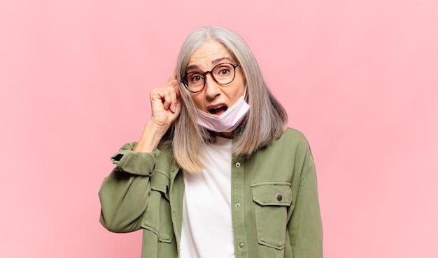 Donna di mezza età che sembra sorpresa, a bocca aperta, scioccata, realizzando un nuovo pensiero, idea o concetto