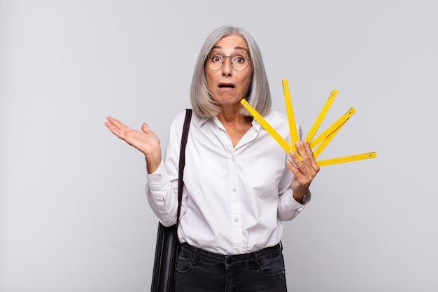 Donna di mezza età che sembra sorpresa e scioccata, con la mascella caduta tenendo un oggetto con una mano aperta sul lato. concetto di architetto