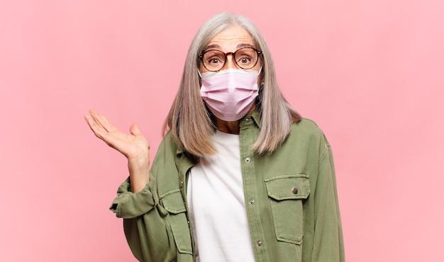 Donna di mezza età che sembra sorpresa e scioccata, con la mascella caduta tenendo un oggetto con una mano aperta sul lato