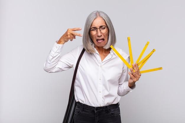 Donna di mezza età che sembra infelice e stressata, gesto di suicidio che fa segno di pistola con la mano, indicando la testa. concetto di architetto