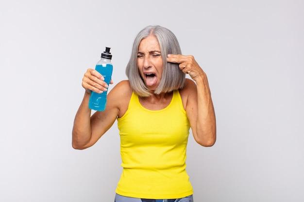 Donna di mezza età che sembra infelice e stressata, gesto di suicidio che fa il segno della pistola