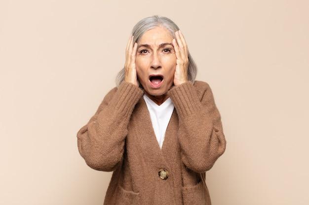 Donna di mezza età che sembra spiacevolmente scioccata, spaventata o preoccupata, con la bocca spalancata e le mani che coprono entrambe le orecchie