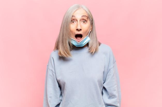 Donna di mezza età che sembra molto scioccata o sorpresa, fissando con la bocca aperta dicendo wow