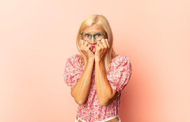 Donna di mezza età che sembra preoccupata, ansiosa, stressata e spaventata, mordendosi le unghie e cercando di copiare lo spazio laterale