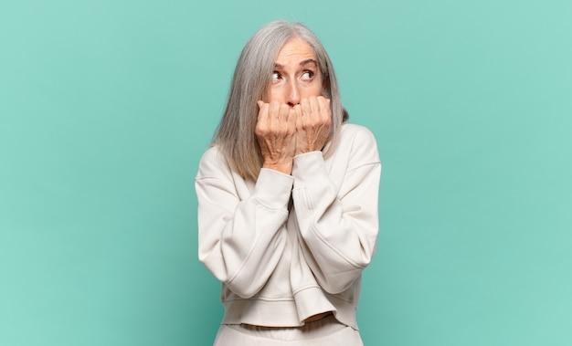 Donna di mezza età che sembra preoccupata, ansiosa, stressata e impaurita, mordendosi le unghie e cercando di copiare lo spazio laterale