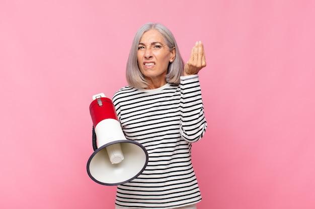 Donna di mezza età che fa un gesto di capice o denaro, dicendoti di pagare i tuoi debiti! con un megafono