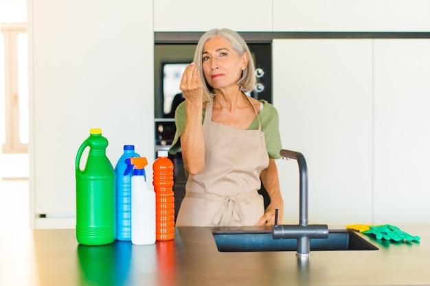 Donna di mezza età che fa gesto di capice o denaro, dicendoti di pagare i tuoi debiti!