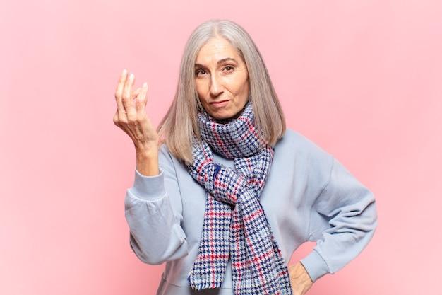 Donna di mezza età che fa un gesto di denaro o di denaro, dicendoti di pagare i tuoi debiti!